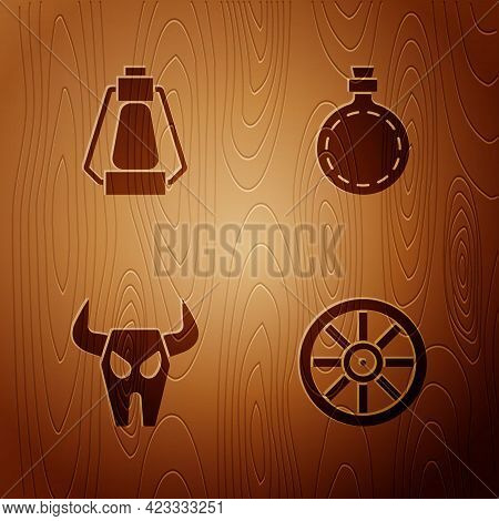 Set Old Wooden Wheel, Camping Lantern, Buffalo Skull And Canteen Water Bottle On Wooden Background.