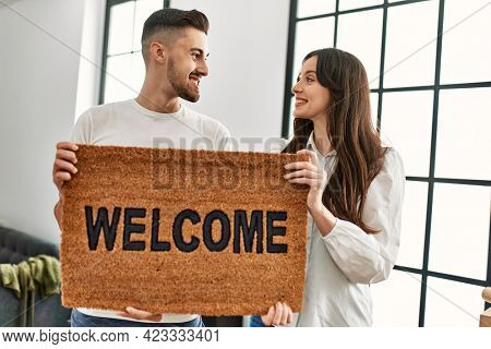 Young hispanic couple smiling happy holding welcome doormat at new home.