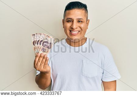 Young latin man holding 500 mexican pesos banknotes looking positive and happy standing and smiling with a confident smile showing teeth