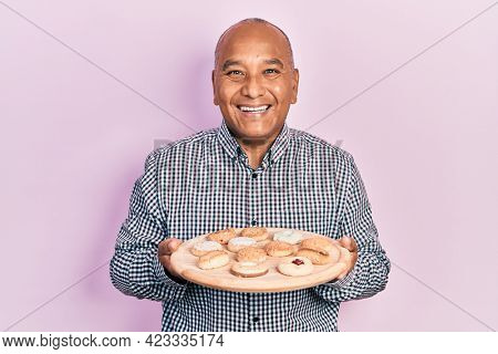 Middle age latin man holding tray with biscuits smiling and laughing hard out loud because funny crazy joke.