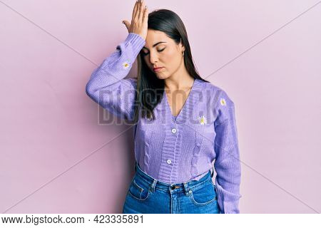 Young brunette woman wearing spring cardigan with flowers print surprised with hand on head for mistake, remember error. forgot, bad memory concept.