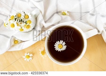 Chamomile Tea With Kitchen Towel And Chamomile In White Ceramic Cup On The Wooden Table. Herbal Tea.