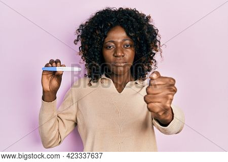 Young african american woman holding pregnancy test result annoyed and frustrated shouting with anger, yelling crazy with anger and hand raised