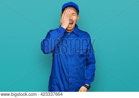 Bald man with beard wearing builder jumpsuit uniform yawning tired covering half face, eye and mouth with hand. face hurts in pain.