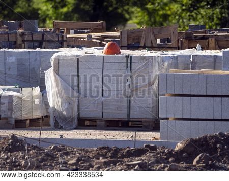 Curbstones Are Stacked In Piles. They Are Wearing A Construction Helmet. Construction Road Works For