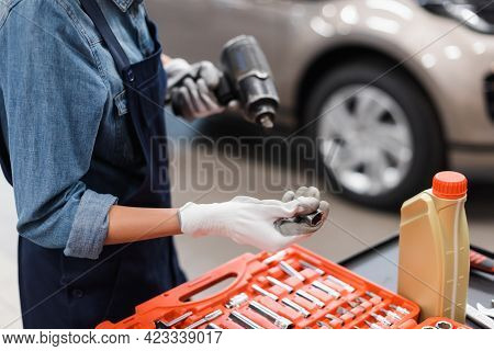 Partial View Of Young Mechanic Hands In Gloves Holding Electric Screwdriver And Attachment Near Tool