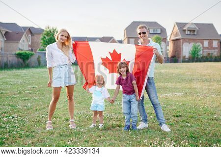 Happy Canada Day. Caucasian Family With Kids Boy And Girl Standing In Park And Holding Large Canadia