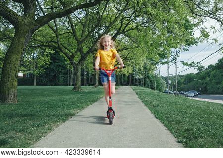 Cute Funny Caucasian Girl Child In Yellow T-shirt Riding Red Scooter On Street Road Park Outdoor. Su