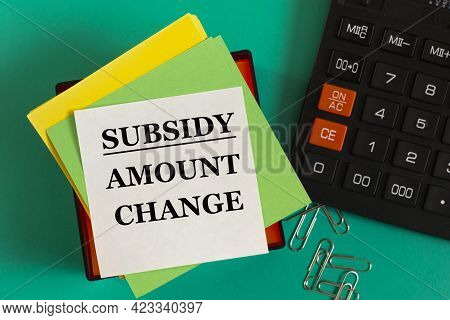 Subsidy Issue Change - Words On Note Paper Against The Background Of A Calculator And Paper Clips. B