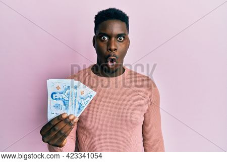 Handsome black man holding 50 thai baht banknotes scared and amazed with open mouth for surprise, disbelief face