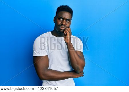 Handsome black man wearing casual white t shirt thinking concentrated about doubt with finger on chin and looking up wondering