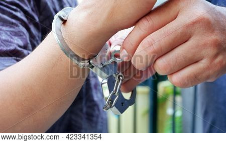 Close Up Police Staff's Hands Unlocking Handcuffs On Male Accused Hand By Key, Focus On Key Handcuff