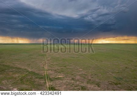 heavy storm cloud over green prairie and distant Rocky Mountains - Pawnee National Grassland in Colorado, aerial view of late spring or early summer scenery