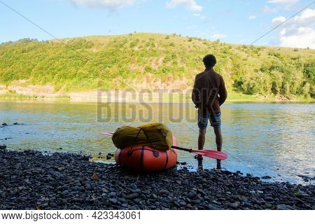Tourist near yellow packraft rubber boat ready for adventures with red padle on a sunrise river. Packrafting. Active lifestile concept
