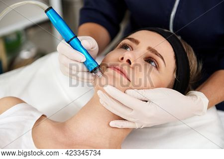 Close-up Shot Of Aesthetician Hand Performing Aqua Peeling Procedure To Young Woman For Exfoliation