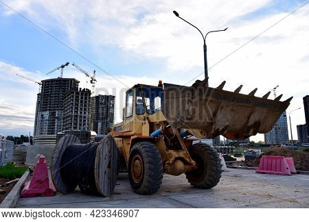 Wheel Loader With A Bucket At Construction. Heavy Machinery For Loading And Unloading Works And Road