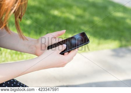 Womens Hands With A Manicure With A Smartphone In Their Hands On The Background Of A Green Lawn