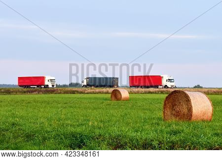View Of A Field With Hay In Rolls Against The Background Of Trucks With Semi-trailer Driving Along T