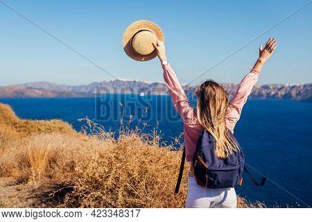 Traveler Woman Walking On Santorini Island, Greece Enjoying Landscape. Happy Girl Raised Arms Enjoyi