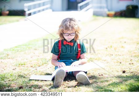 Smart Curious Nerd In Glasses Reading Book Study With Copybook Outdoor, School Education