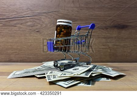 Pills In A Shopping Basket On A Heap Of American Dollars. Economy Concept Of Spending Money On Medic