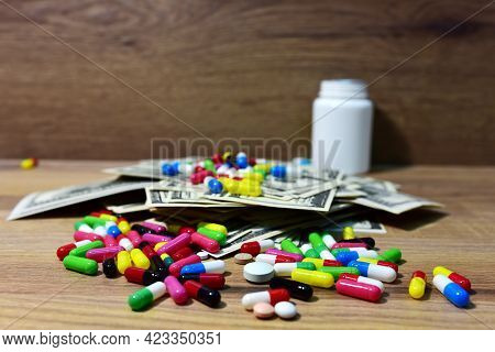 Pills In On A Heap Of American Dollars. Economy Concept Of Spending Money On Medicines And Pills. Me