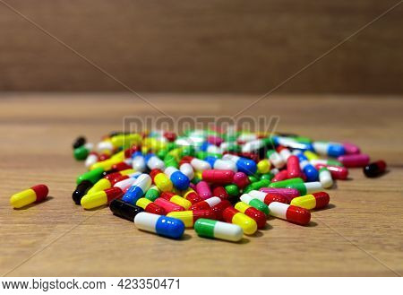 Pills In Multicolored Capsules On Wooden Background. Pharmaceutical Pills, Medical Tablets. Medical