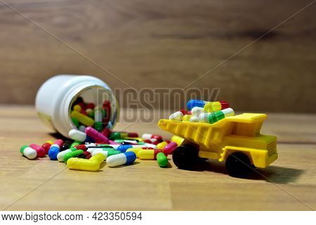 Many Multi-colored Pills In Campuses Against The Background Of A Medical Plastic Bottle For Pills. T