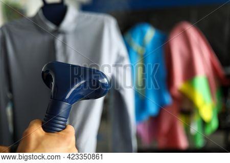 Hand Holds Garment Steamer Near Shirt Close-up