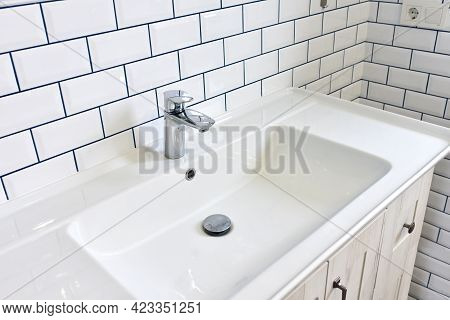 Modern Bathroom Interior With Design Washbasin On A Background Of White Ceramic Tiles. Faucet For Wa