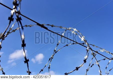 Barbed Wire Against The Blue Sky. Detention Concept And Forbidden Territory
