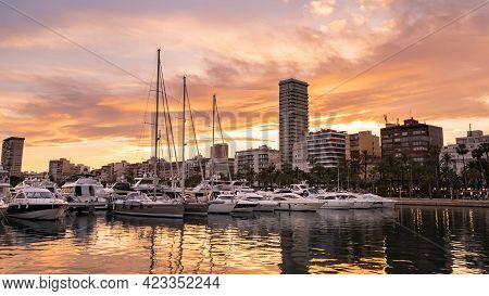 Alicante Harbor With Luxury Yachts And Sailboats, Promenade Palm Trees In Old Town At Sunset, Spain.