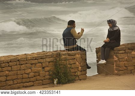 Rabat, Morocco. 25 September 2017. A Young Pair Sits On The Embankment By The Ocean, Rabat, Morocco.