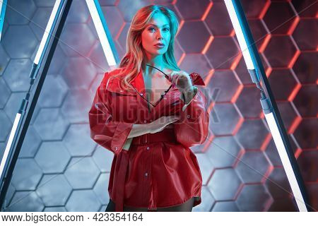 Modern middle-aged woman in red leather jacket posing in the light of neon lamps. Techno style, disco. Fashion shot.