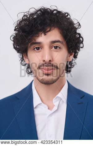 Men's beauty. Portrait of a handsome brunet man in elegant blue suit and a bow-tie looking at the camera friendly. Businessman portrait. Studio shot on a white background.