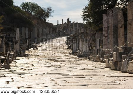 Historic marble slabs of the Curetes street in Ephesus Ancient City at sunny day in Selcuk, Turkey. Ancient and historical road from the roman period. Selective focus