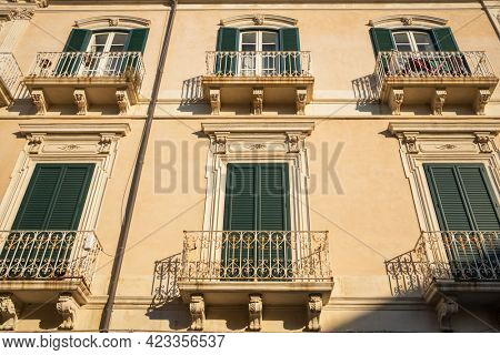 Building exterior with windows and balconies in Sicily, Italy. Typical sicilian facade of the building.