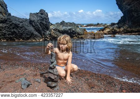 The Boy Kid Is Concentrating On Building Towers Of Stones Against Seashore. Summer Kids Holidays. Ch