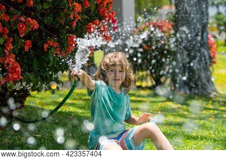 Cute Boy Watering Plants In The Garden At Summer Day. Child With Garden Tools And Watering Hose In B