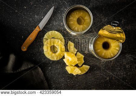 Canned sliced pineapple fruit on a black table. Top view.