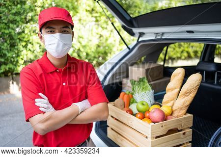 Asian Deliver Man Wearing Face Mask In Red Uniform Handling Bag Of Food, Groceries, Fruit Give To Wo