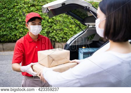 Asian Delivery Man Carry Box From Car Trunk To Deliver To Girl Customer At House. Male Postman Weari