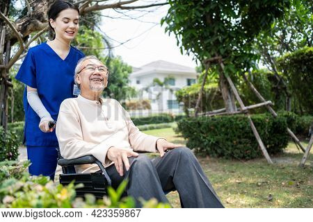 Asian Happy Senior Retired Grandfather Have Fun Outdoor At Green Park With Young Woman Nurse. Caregi