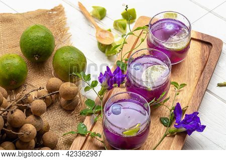 Glass Of Lemon Juice, Pea Flowers And Longan On White Wooden Table.