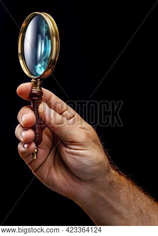 Old fashioned handle magnifier or hand lense in man's hand isolated on black background.