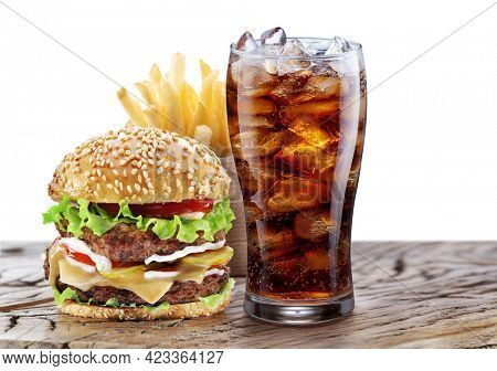 Delicious hamburger with cola and potato fries isolated on wooden table and on white background. Fast food concept.