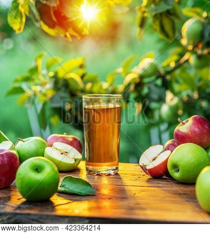 Fresh apple juice and apples on wooden table in the summer orchard garden.