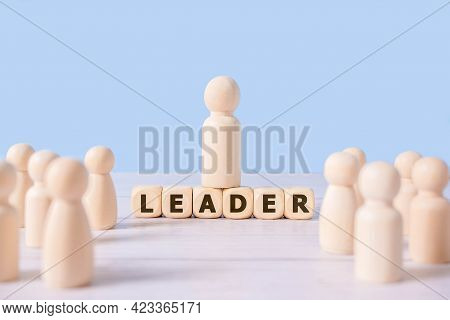 Leader word On Wooden Blocks And Group Of Wooden Figure On Blue Background.successful Team Leader,