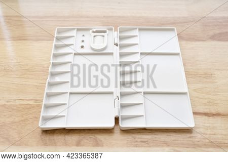 White Watercolour Palette. Empty Watercolor Tray Isolated On Wood Background.