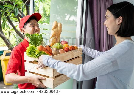 Asian Deliver Man Worker In Red Color Uniform Handling Bag Of Food, Fruit, Vegetable Give To Young B